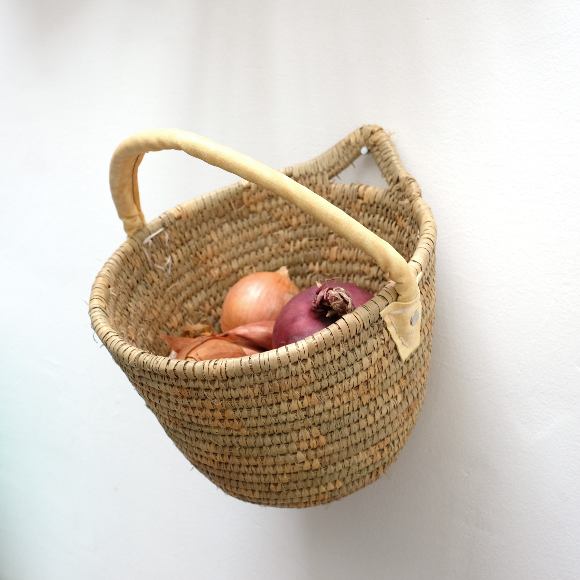 Woven basket with a faux leather handle.